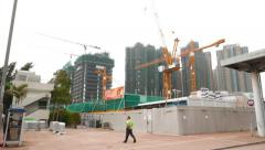 Man walk against construction site, tracking shot, Hung Hom area Stock Footage