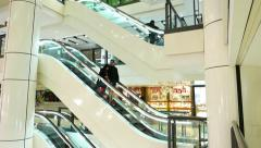 Asian couple travel down on escalator in mall, low angle tracking shot - stock footage