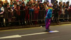 Clown on small segway like self-balancing scooter, against spectators crowd Stock Footage
