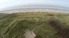 Aerial bird eye view drone flying over grass dunes heading for deserted beach 4k Stock Footage
