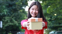 Teen girl Chinese dress, happy new year and give gift, relax and smile. Stock Footage