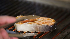 Chef roasting salmon steak on the grill slowmotion Stock Footage