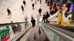 People climb up and go down the escalator with hand luggage at the airport Stock Footage