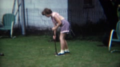 1956: Girl in pink tube top playing croquet game in backyard grass field.  - stock footage