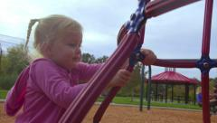 Little girl tries to climb jungle gym - stock footage