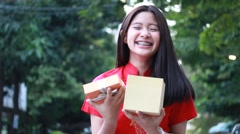 Thai teen beautiful girl in Chinese dress, open box gift, smile and very happy. Stock Footage