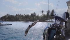 Man jumping from sailboat into caribbean islands of San Blas. Slow Motion. Stock Footage