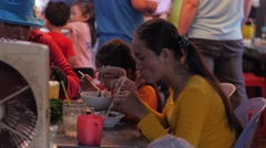 Woman and girls eating with chopsticks in market,Phnom Penh,Cambodia - stock footage