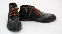 It is snowing - new winter boots standing in the snow Stock Footage