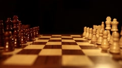 Side shot of a chess board on a black background and the chess pieces lined up Stock Footage
