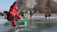 In winter, people catch fish from under the ice in the river. Russia. Stock Footage