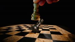 A white chess piece king overthrows the black king on a chess board - stock footage