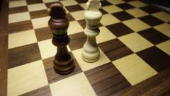 A black king in the front on a chess board, and a white king joins him Stock Footage