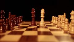 Two king chess peces standing in the middle of a chess board among other pieces Stock Footage
