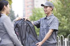 Young woman getting dry-cleaned clothes from delivery person - stock photo