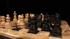 A black knight eats a white pawn in a chess game, isolated on black background - stock footage