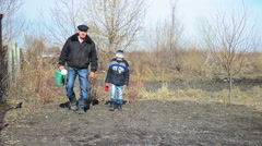 Grandfather with his grandson in the early spring are watering the trees and Arkistovideo
