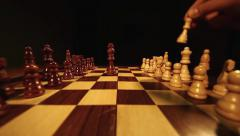 Two kings being brought and put in the center of a chess board,isolated on black - stock footage