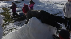 A family making snow men and a slide from the snow Stock Footage
