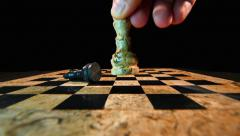 The white king throws down the black king on a chess board Stock Footage