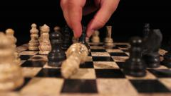A black queen hits the white king and throws him down on a chess board Stock Footage