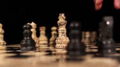 A black bishop hits the white king piece and it falls down on the chess board Stock Footage