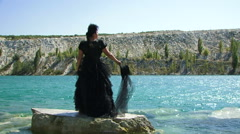 Woman In Black Standing On Rock Near Lake Stock Footage