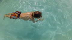 Child swimming underwater in a pool Stock Footage