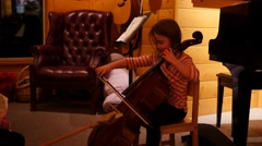 Stock Video Footage of Girl plays cello during family christmas party nativity