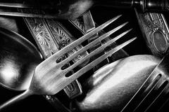 Abstract black and white photo of mixed silver forks, spoons and knives - stock photo