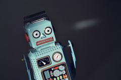 Vintage tin toy robot isolated on black background, filtered retro photo - stock photo