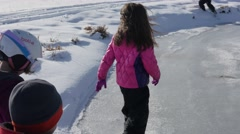 Little kids playing on frozen ice on a small pond Stock Footage