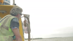Fisherman hauling lobster creel off the side of a small fishing boat Stock Footage