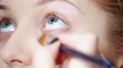 Make-up artist applying mascara to model's eyelashes - stock footage