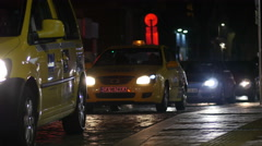 Night traffic taxi car headlights and pedestrians in Sofia Bulgaria Stock Footage