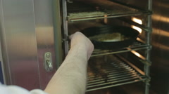 Fish in a saucepan being placed in the oven Stock Footage