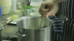 Chef in a kitchen stirring a large pot Stock Footage