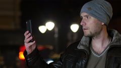 Young man taking pictures via smartphone on a night cold winter street Stock Footage