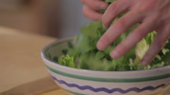 Chef in a kitchen preparing a salad bowl Stock Footage
