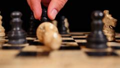 Footage of a chess board and a player hits the white king piece which falls down - stock footage