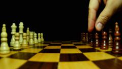 Side shot of chess pieces on a chess board and a man making his first move Stock Footage