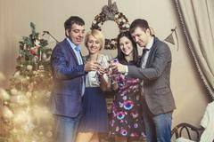 Friends of four men and women with bacale celebrate with champagne - stock photo