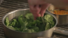 Spinach being tossed in a pan by a chef in a kitchen Stock Footage