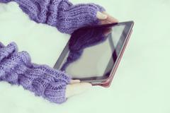 Woman hands in light teal knitted mittens are holding modern tablet pc on sno - stock photo