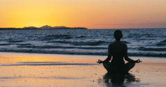 Silhouette woman practicing yoga on beach at sunset, new years resolution Stock Footage