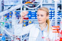 Chemical laboratory scene: attractive young student scientist observing the b - stock photo