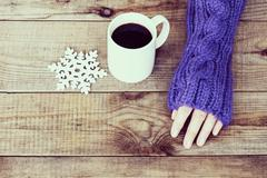 Woman hand in teal glove, mug with hot coffee or cocoa and snowflake on woode - stock photo