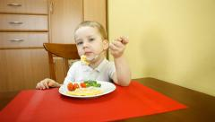 Child seating at the table and eating - stock footage