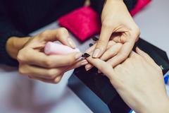 Manicure. Beauty saloon. Close-up. Apply black nail polish Stock Photos