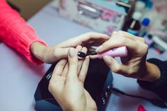 Manicure. Beauty saloon. Close-up. Apply black nail polish. - stock photo